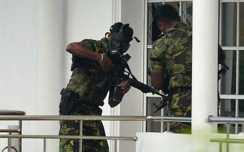 Sri Lankan Special Task Force (STF) personnel in gas masks are pictured outside a house during a raid  - Credit: AFP/ISHARA S. KODIKARA