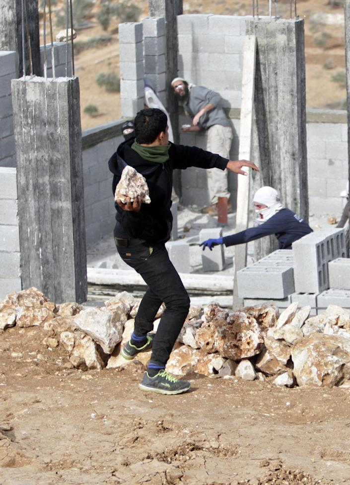 """A Palestinian throws stones at Israeli settlers before they were detained by Palestinian villagers in a building under construction near the West Bank village of Qusra, southeast of the city of Nablus, Tuesday, Jan. 7, 2014. Palestinians held more than a dozen Israeli settlers for about two hours Tuesday in retaliation for the latest in a string of settler attacks on villages in the area, witnesses said. The military said the chain of events apparently began after Israeli authorities removed an illegally built structure in Esh Kodesh, a rogue Israeli settlement in the area. In recent years, militant settlers have often responded to any attempts by the Israeli military to remove parts of dozens of rogue settlements, or outposts, by attacking Palestinians and their property. The tactic, begun in 2008, is known as """"price tag."""" (AP Photo/Nasser Ishtayeh)"""