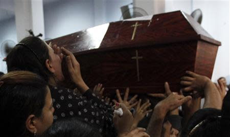 Relatives of four victims killed in an attack at a wedding on Sunday, attend their funerals at Virgin Church in Cairo