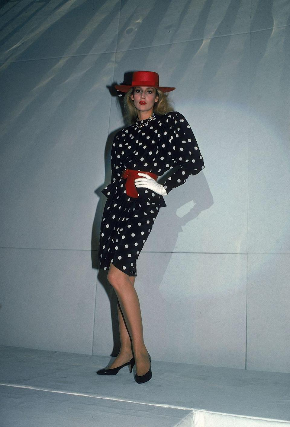 <p>Jerry Hall models a polka-dot dress, red wide-brim hat, and a matching belt.</p>