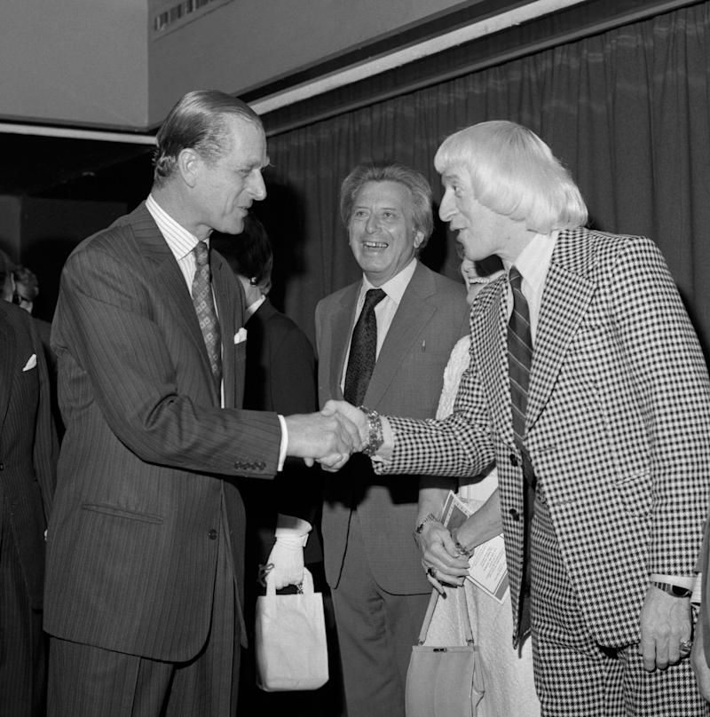 Guest of honour, The Duke of Edinburgh, shaking hands with show business personality Jimmy Savile (r), watched by Sir Bernard Delfont (c), at the Variety Club of Great Britain's luncheon. The luncheon was in aide of the Variety Club's National Sponsored Walk, part of the Club's International 1975 annual convention. (Photo by PA Images via Getty Images)