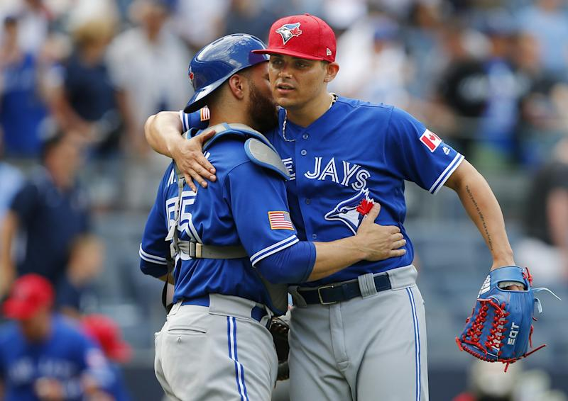 Catcher Russell Martin #55 of the Toronto Blue Jays and closer Roberto Osuna #54 embrace after their 4-1 win over the New York Yankees during a game at Yankee Stadium on July 4, 2017 in the Bronx borough of New York City.