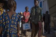 Tigray refugees who fled the conflict in Ethiopia's Tigray region, receive aid from the UNHCR at Umm Rakouba refugee camp in Qadarif, eastern Sudan, Tuesday, Nov. 24, 2020. (AP Photo/Nariman El-Mofty)