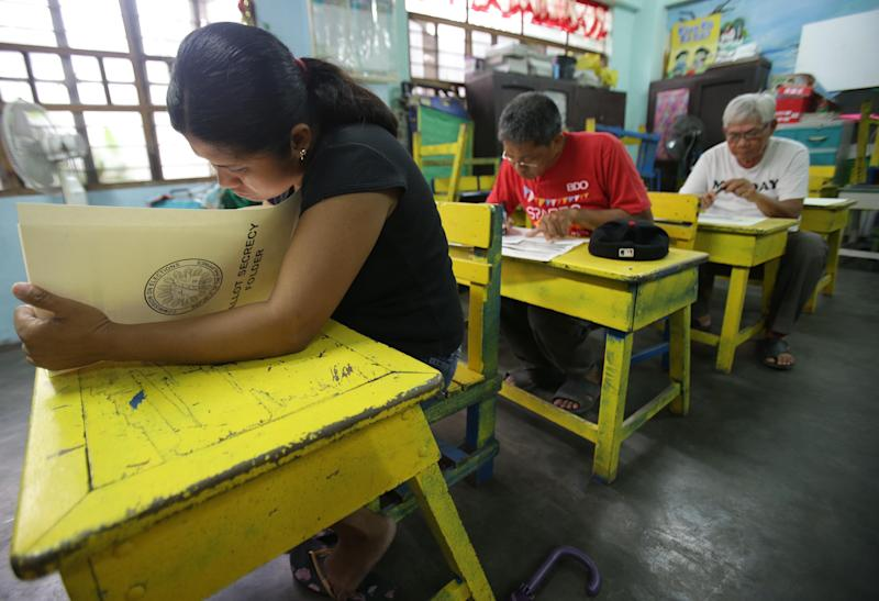 Filipinos fill out ballots at a classroom used as a voting precinct during mid-term elections at a school in Manila, Philippines on Monday, May 13, 2013. The country is electing local officials from senators to congressmen and down to municipal mayors during Monday's mid-term elections. (AP Photo/Aaron Favila)