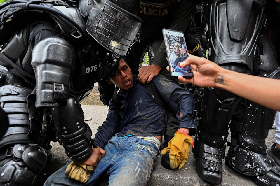 TOPSHOT - Colombian police officers arrest a demonstrator during a protest against the government in Cali, Colombia, on May 10, 2021. - Faced with angry street protests and international criticism over his security forces' response, Colombia President Ivan Duque is coming across as erratic and out of touch with a country in crisis, analysts say. Since April 28, hundreds of thousands of people have vented their frustrations against the government after poverty and violence soared during the pandemic. (Photo by Luis ROBAYO / AFP) (Photo by LUIS ROBAYO/AFP via Getty Images)