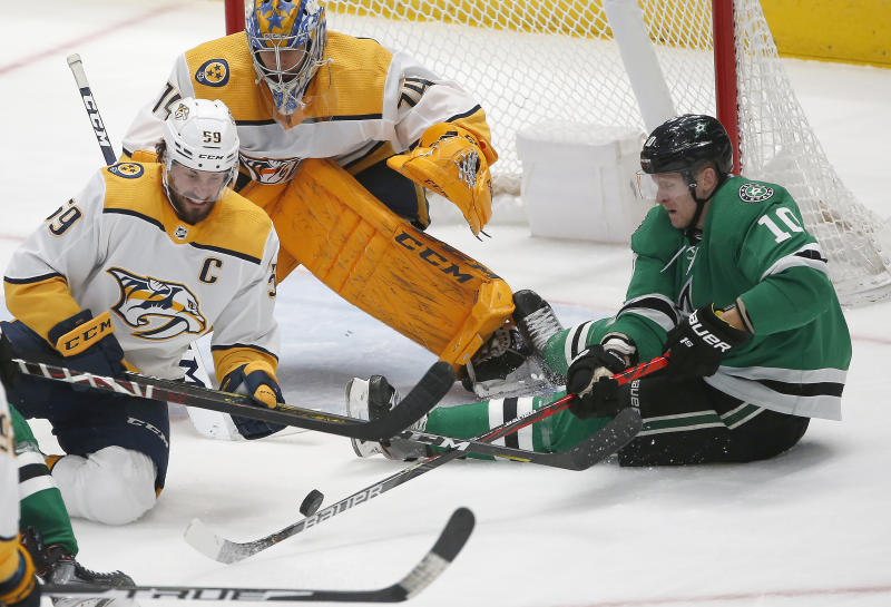 Nashville Predators defenseman Roman Josi (59) and Dallas Stars right wing Corey Perry (10) battle for the puck as Predators goaltender Juuse Saros (74) looks on during the second period of an NHL hockey game Saturday, March 7, 2020, in Dallas. (AP Photo/Ron Jenkins)