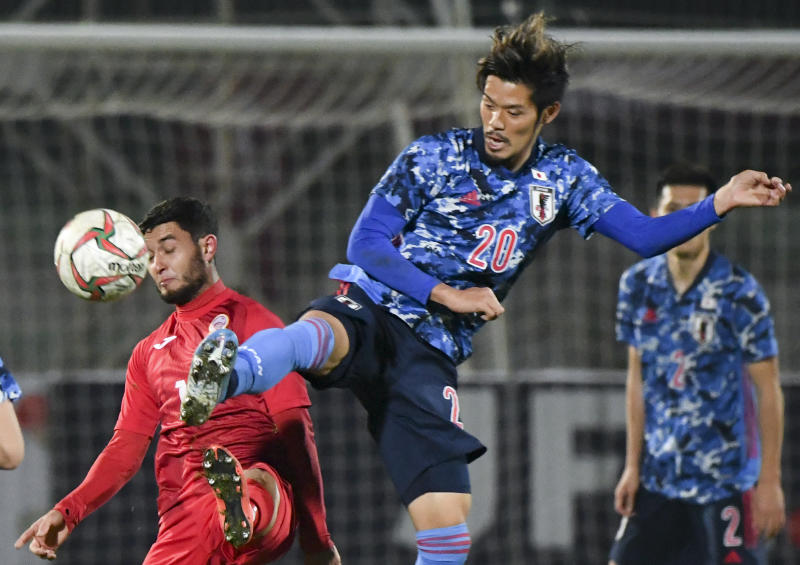 Japan's Yamaguchi Hotaru, right, fights for the ball with Kyrgyzstan's Murolimzhon Akhmedov during the World Cup 2022 Qualifying Asian zone Group F soccer match between Kyrgyzstan and Japan in Bishkek, Kyrgyzstan, Thursday, Nov. 14, 2019. (AP Photo/Vladimir Voronin)