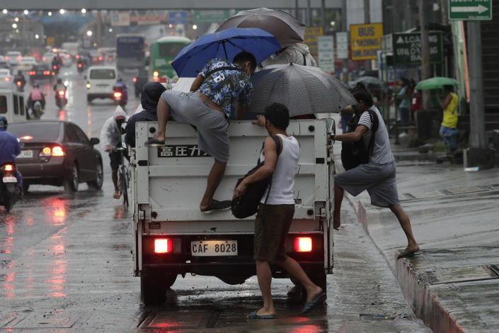 Workers climb on to a truck for a free ride as rain caused by Typhoon Vamco started to pour in Quezon city, Philippines on Wednesday, Nov. 11, 2020. Typhoon Vamco blew closer Wednesday to a northeastern Philippine region still struggling to recover from a powerful storm that left a trail of death and destruction just over a week ago, officials said, adding that thousands of villagers were being evacuated again to safety. (AP Photo/Aaron Favila)