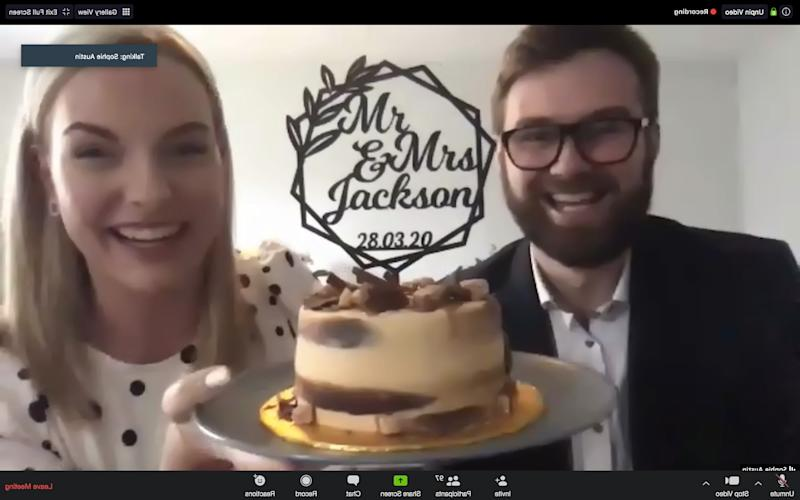Ben Jackson and Sophie Austin of the school sweethearts holding their wedding cake as they get married over Zoom video chat, after the Coronavirus lockdown made their dream wedding impossible.