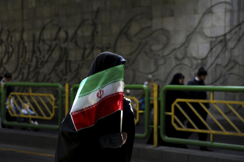 FILE - In this Feb. 11, 2016 file photograph, an Iranian woman holds the national flag during a rally commemorating the 37th anniversary of the Islamic revolution, in Tehran, Iran. Iran's 1979 Islamic Revolution initially inspired both Islamic militants and Islamists across the Mideast. They saw the revolution as the starting gun in a competition to push out the strongman Arab nationalism that had taken hold across the Middle East. However, analysts say Iran's push to back militants in the wider Mideast and Saudi Arabia's efforts to mobilize the Sunni world against the Shiite power would turn many away. (AP Photo/Ebrahim Noroozi, File)