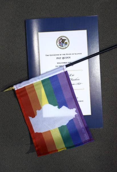 A program and an Illinois rainbow flag is placed on a seat for spectators who will witness Illinois Gov. Pat Quinn signing the Religious Freedom and Marriage Fairness Act, during ceremonies on the campus of the University of Illinois Chicago Wednesday, Nov. 20, 2013, in Chicago. (AP Photo/Charles Rex Arbogast)