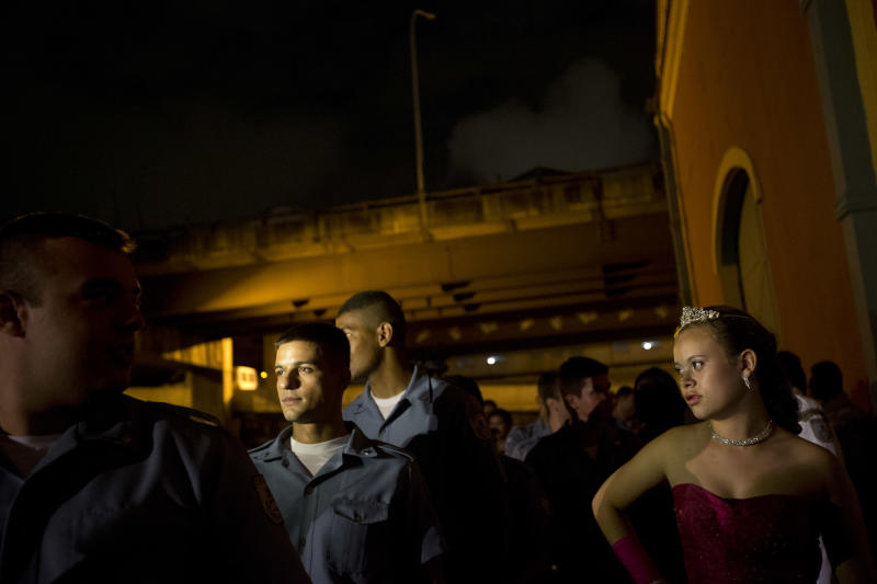A 15-year-old girl stands next to police officers as they wait to enter the hall for a debutante ball organized by the Pacifying Police Unit program, in Rio de Janeiro, Brazil, Thursday, Dec. 19, 2013. The event marked the five-year anniversary of the pacifying police units, or UPPs - police battalions that have re-conquered slums that were ruled for decades by drug-dealing gangs and where police long feared to tread. Officers in spotless uniforms gingerly held onto the debutantes' hands as the girls paraded into the hall in their evening finest. (AP Photo/Silvia Izquierdo)