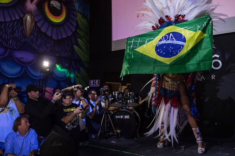 Rosie Oliveira from Amazonas holds a Brazilian national flag with an inscription reading 'Temer out' (a reference to Brazilian President Michel Temer) during the Miss Bumbum Brazil 2017 pageant in Sao Paulo. (NELSON ALMEIDA via Getty Images)