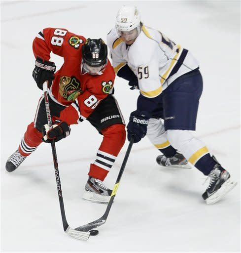 Chicago Blackhawks right wing Patrick Kane (88) takes a backhand shot on goal as Nashville Predators defenseman Roman Josi (59) reaches for the puck during the second period of an NHL hockey game Tuesday, Jan. 24, 2012, in Chicago. (AP Photo/Charles Rex Arbogast)