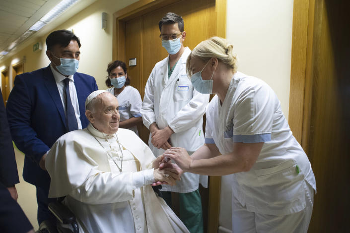 Pope Francis is greeted by hospital staff as he sits in a wheelchair inside the Agostino Gemelli Polyclinic in Rome, Sunday, July 11, 2021, where he was hospitalized for intestine surgery. (Vatican Media via AP)