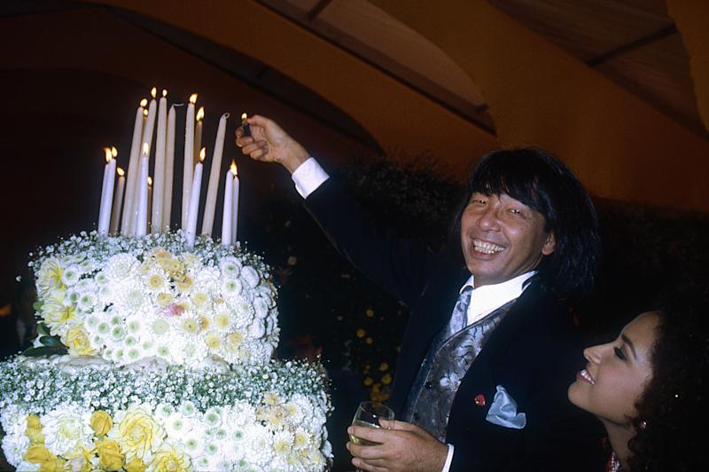 Japanese designer Kenzo Takada lights the candles on a large flower-covered cake. He is showing his women's 1991 spring-summer ready-to-wear line in Paris. (Photo by Pierre Vauthey/Sygma/Sygma via Getty Images)