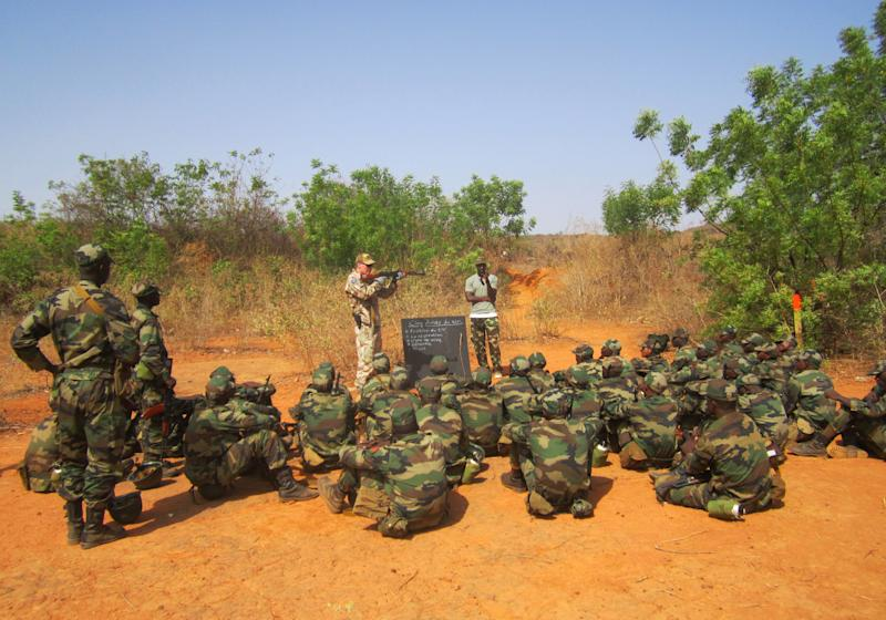 In this photo taken Monday, April 8, 2013, a Swedish instructor explains the steps for firing a weapon, during a European Union training session in the village of Koulikoro, 60 kilometers (37 miles) outside Bamako, Mali. In preparation for the final pullout of French troops from Mali, a European Union team has started training Malian soldiers for battle against jihadists who overran much of this west African country before they were pushed back by a French military intervention. (AP Photo/Baba Ahmed)