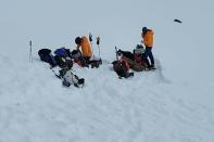 Alaska Mountain Rescue Group volunteers assemble near the site of a helicopter crash which killed five people
