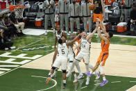 Phoenix Suns guard Devin Booker, right, shoots over Milwaukee Bucks guard Jeff Teague (5) and guard Pat Connaughton (24) during the second half of Game 4 of basketball's NBA Finals in Milwaukee, Wednesday, July 14, 2021. (AP Photo/Paul Sancya)