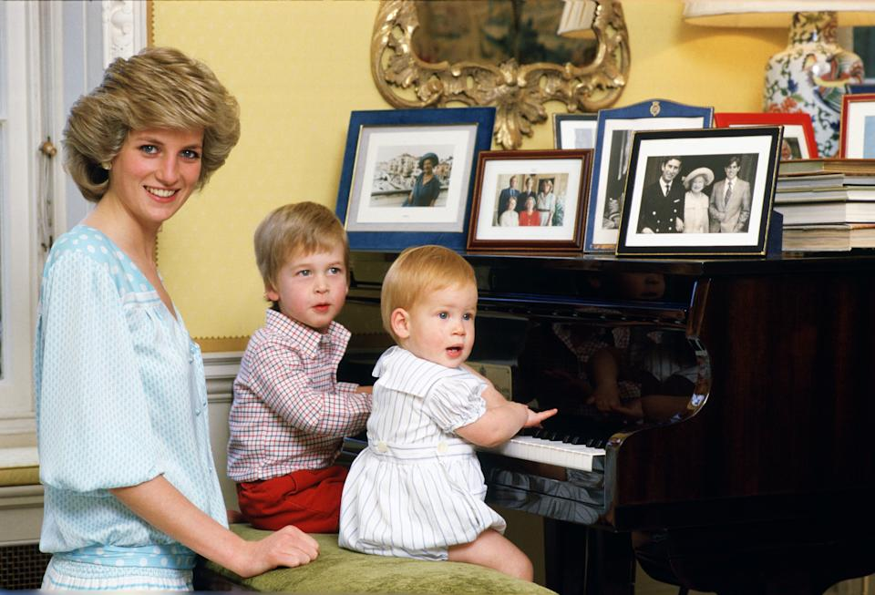 Diana, Princess of Wales with her sons, Prince William and Prince Harry sitting at the piano in Kensington Palace [Photo: Getty]