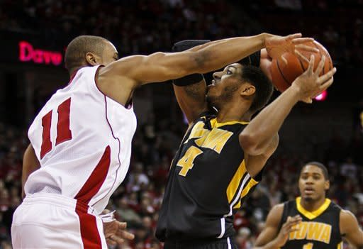 Wisconsin's Jordan Taylor (11) reaches in on Iowa's Roy Devyn Marble during the first half of an NCAA college basketball game Saturday, Dec. 31, 2011, in Madison, Wis. (AP Photo/Andy Manis)