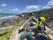 In this April 13, 2021 photo provided by Kevin O'Brien, workers with the Papahanaumokuakea Marine Debris Project remove fishing nets and plastic from the shoreline of Lisianski Island in the Northwestern Hawaiian Islands. A crew has returned from the remote Northwestern Hawaiian Islands with a boatload of marine plastic and abandoned fishing nets that threaten to entangle endangered Hawaiian monk seals and other marine animals on the tiny, uninhabited beaches stretching for more than 1,300 miles north of Honolulu. (Kevin O'Brien, Papahānaumokuākea Marine Debris Project via AP)