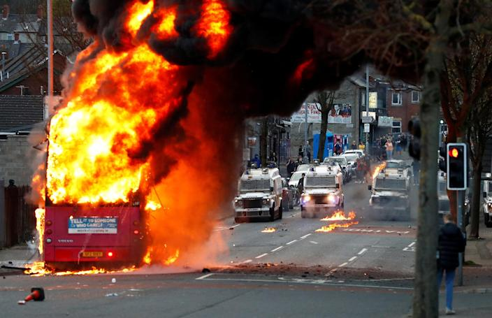 Police vehicles are seen behind a hijacked bus burns on the Shankill Road as protests continue in Belfast, Northern Ireland, April 7.