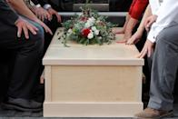 Relatives touch one of the coffins containing the remains of Dawna Ray Langford and her sons Trevor and Rogan, who were killed by unknown assailants, to be buried at the cemetery in La Mora