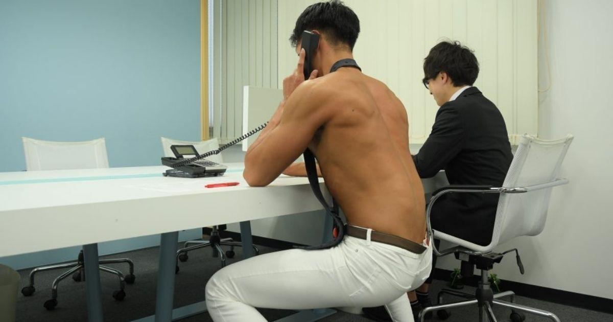 A shirtless guy crouching at an office desk answering the phone. (Photo courtesy of freephotomuscle.com)