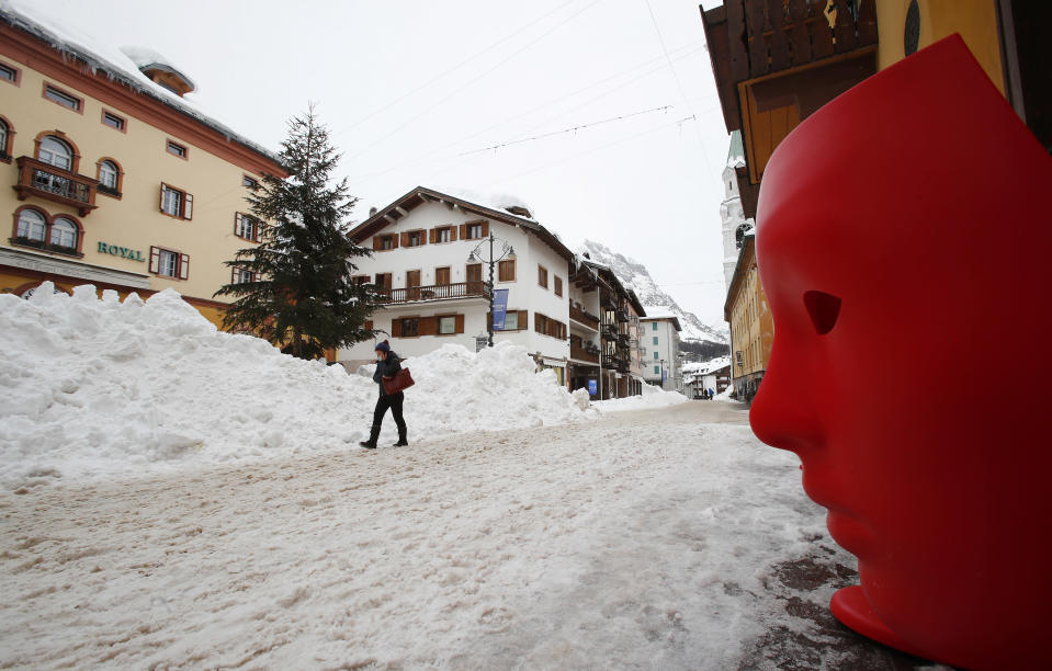 FILE - In this Jan. 28, 2021 file photo, a woman walks through a street in Cortina D'Ampezzo, Italy. On the eve of what was supposed to finally be the repeatedly delayed opening of Italy's ski slopes, the government on Sunday, Feb. 14, 2021, yanked permission because a coronavirus variant was found to be circulating in a good portion of recently infected persons. Health Minister Roberto Speranza's ordinance forbids amateur skiing at least until March 5. (AP Photo/Antonio Calanni)