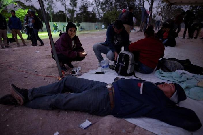 People, part of a caravan of migrants heading toward the United States, rest at the border between Honduras and Guatemala in Agua Caliente