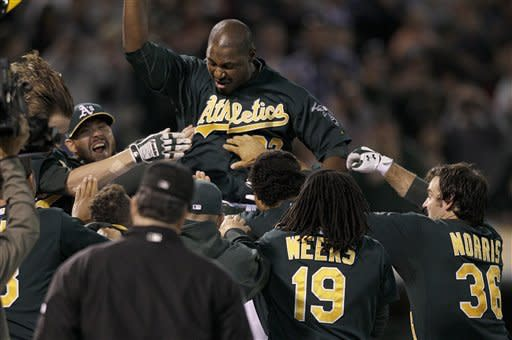 Oakland Athletics ' Chris Carter, top, celebrates after hitting a three-run home run during the eleventh inning of a baseball game against the Seattle Mariners in Oakland, Calif., Friday, July 6, 2012. The Athletics won 4-1 in 11 innings. (AP Photo/Jeff Chiu)