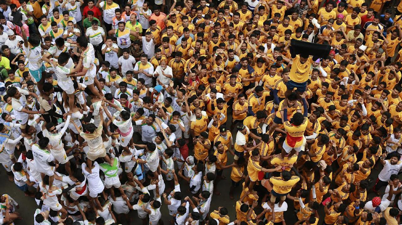 <p>Indian devotees show a black flag standing on the top of a human pyramid before breaking dahi handi, a pot filled with curd, during a protest against an Indian court order imposing height restrictions on human pyramids formed during the festivities and banning youngsters below 18 years from participating, in Mumbai, India, Aug. 25, 2016. The holiday marks the birth of the Hindu God Krishna. (Photo: Rafiq Maqbool/AP) </p>