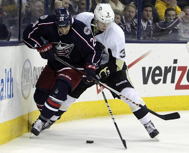 Columbus Blue Jackets' Derek MacKenzie, left, and Pittsburgh Penguins' Olli Maatta, of Finland, fight for a loose puck during the second period of an NHL hockey game, Sunday, Dec. 29, 2013, in Columbus, Ohio. (AP Photo/Jay LaPrete)