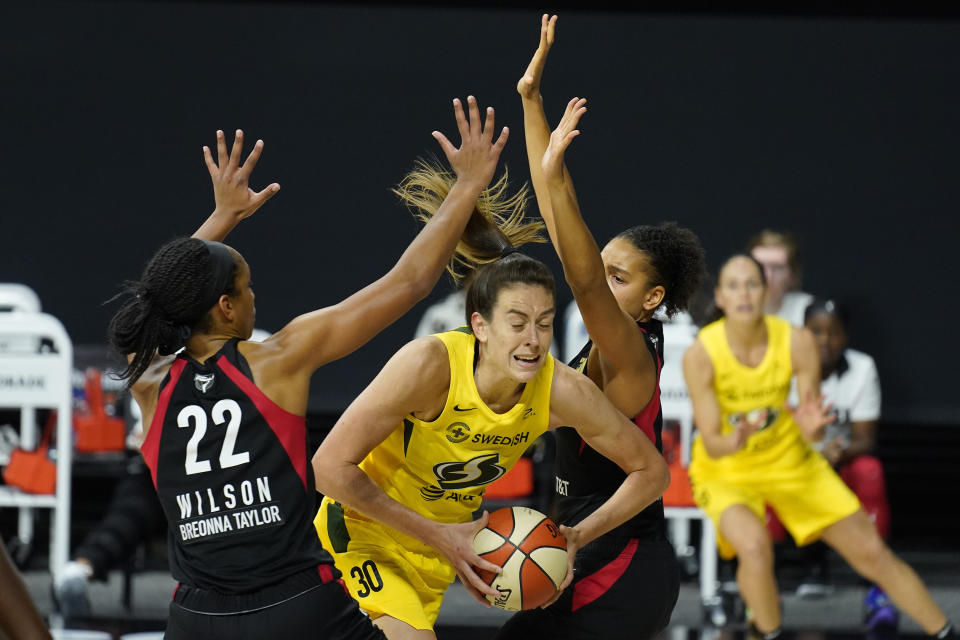 FILE - Seattle Storm forward Breanna Stewart (30) gets between Las Vegas Aces center A'ja Wilson (22) and forward Cierra Burdick (11) during the second half of Game 3 of basketball's WNBA Finals in Bradenton, Fla., in this Tuesday, Oct. 6, 2020, file photo. The WNBA will tip off its 25th season on Friday, May 14, 2021. (AP Photo/Chris O'Meara)