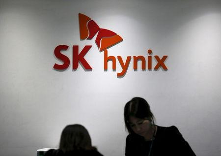 Employees talk in front of the logo of SK Hynix at its headquarters in Seongnam, South Korea, April 25, 2016. REUTERS/Kim Hong-Ji/Files