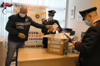 Italian Carabinieri wrap up confiscated cacti to be sent back to Chile, in Milan, Italy, Wednesday, April 7, 2021. A huge cactus bust in Italy in February 2020 resulted in the confiscation of over 1,000 rare cacti. The find became the catalyst for an international effort among cacti experts, police, conservationists and governments to launch the first rare plant return to its native habitat. (Carabinieri via AP)