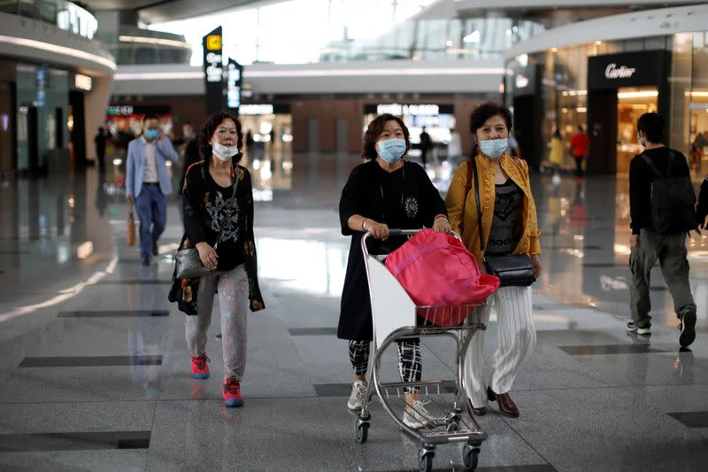 People wearing face masks are seen at the Beijing Daxing International Airport, ahead of Chinese National Day holiday, in Beijing