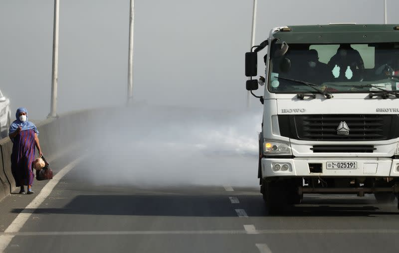 A woman wearing a face mask walks next to a truck spraying disinfectant on the street as part of measures to prevent the potential spread of coronavirus (COVID-19), in Addis Ababa