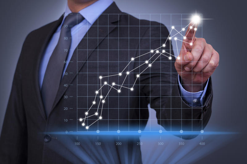 Man in a suit pointing to an upward trending series of data points on a graph.