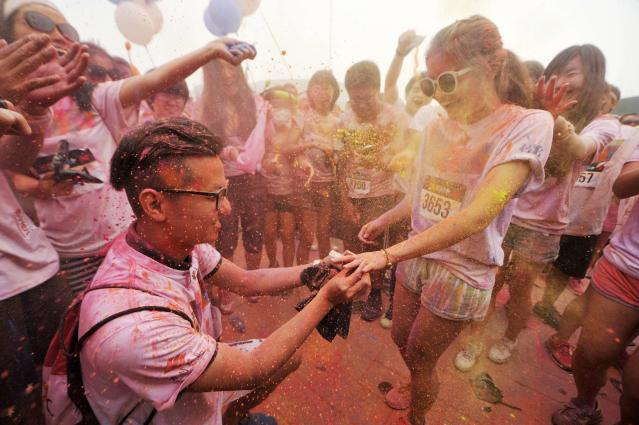 A man (bottom L) propose to his girlfriend as they are sprayed with colour powder during a five-kilometre colour run event in Beijing June 21, 2014. REUTERS/China Daily (CHINA - Tags: SPORT ATHLETICS SOCIETY) CHINA OUT. NO COMMERCIAL OR EDITORIAL SALES IN CHINA