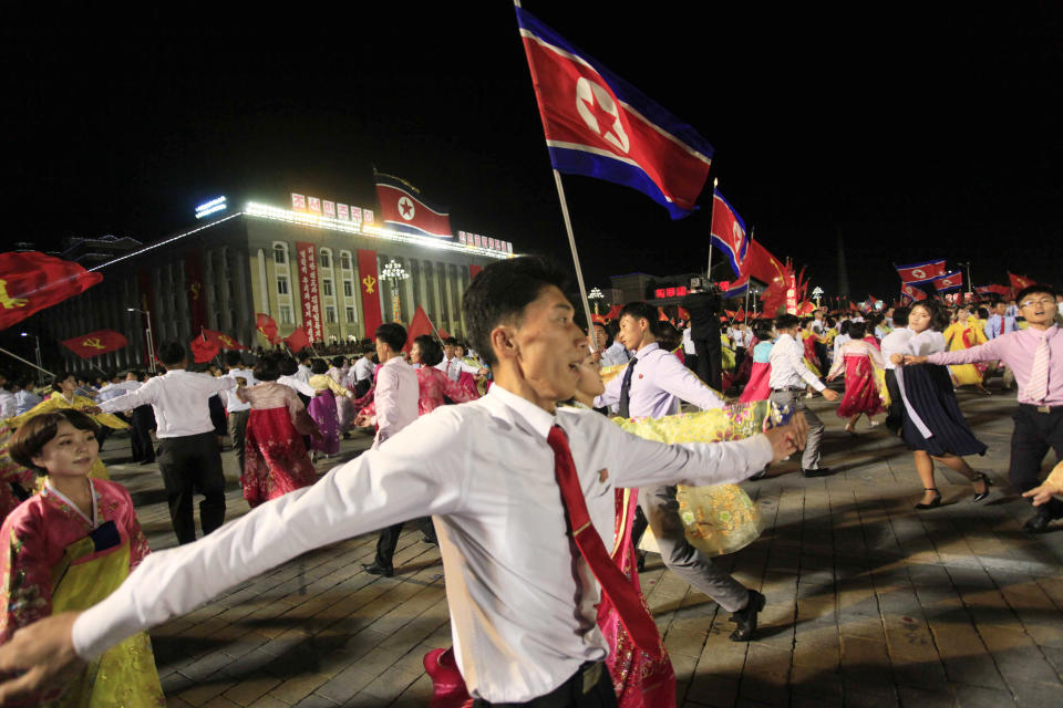 North Korean men and women participate in a mass dance event marking the 20th anniversary of the election of former leader Kim Jong Il as general secretary of the Workers' Party. (AP Photo/Jon Chol Jin)
