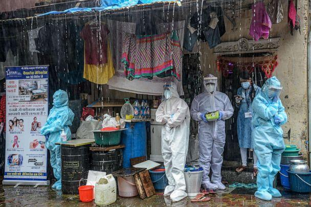 PHOTO: Health workers wearing personal protective equipment suits take shelter amid heavy rain while conducting a COVID-19 screening in Mumbai, India, on Aug. 12, 2020. (Indranil Mukherjee/AFP via Getty Images)