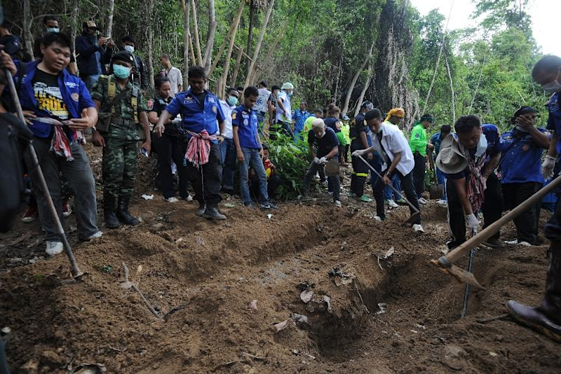 Rescue workers and forensic experts dig out skeletons from shallow mass graves at an abandoned jungle camp in the Sadao district of Thailand's southern Songkhla province, on May 2, 2015 (AFP Photo/Madaree Tohlala)