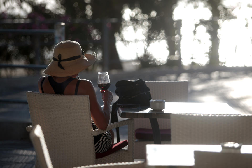 A woman sits in a terrace bar near the beach of Palma de Mallorca, Spain, Monday, June 15, 2020. Borders opened up across Europe on Monday after three months of coronavirus closures that began chaotically in March. (AP Photo/Joan Mateu)