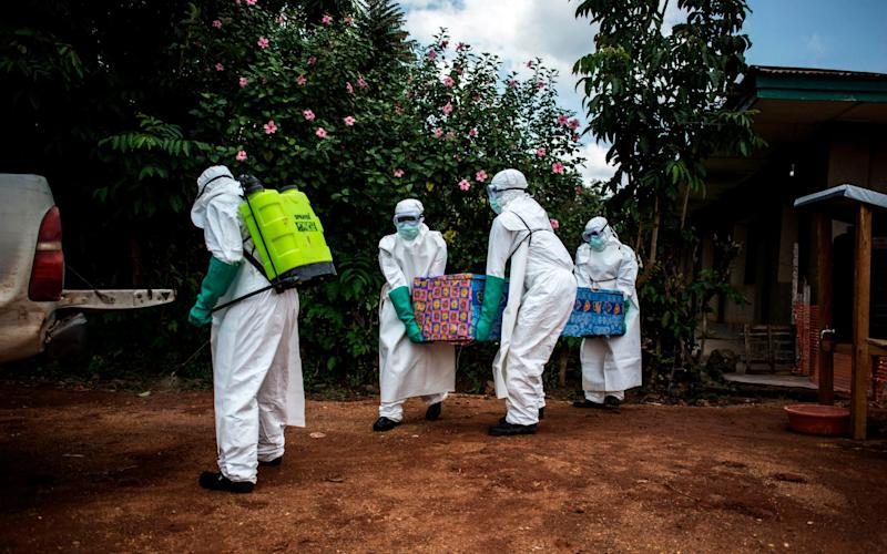 Health workers near Beni carry the body of an Ebola victim out of their home to perform a safe burial - John WESSELS / AFP