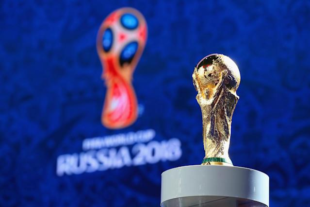 The World Cup trophy is displayed in front of the official logo for the 2018 World Cup in Russia. (Getty)