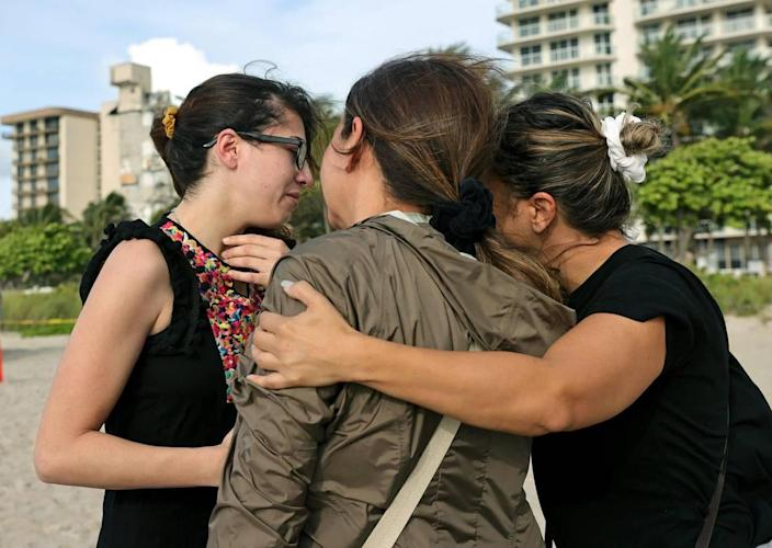 From left to right, Fayzah Bushnaq, Maria Fernanda Martinez and Mariana Cordeiro comfort each other next to the Champlain Towers South Condo in Surfside, Florida, Friday, June 25, 2021. The apartment building partially collapsed on Thursday, June 24.