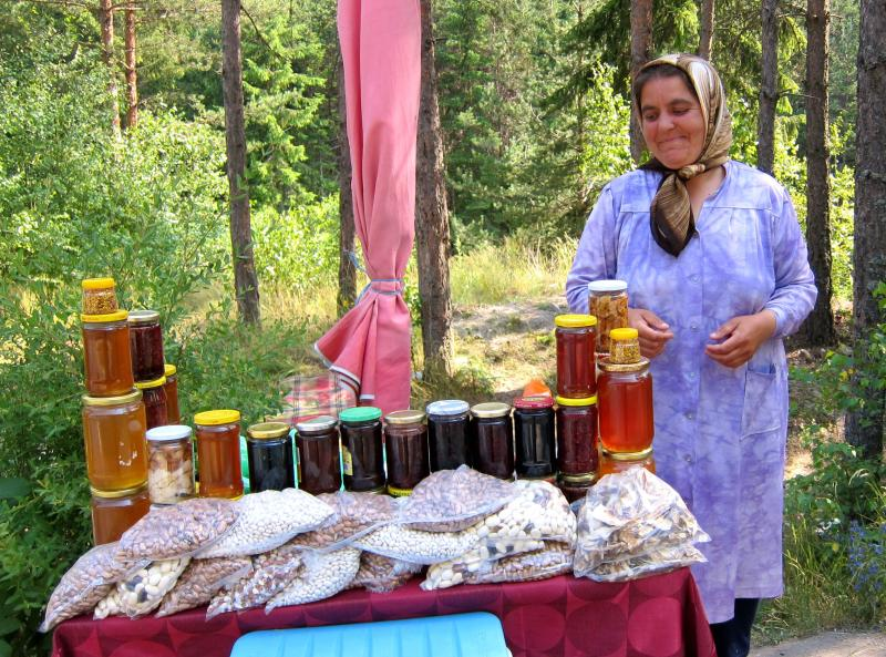 This July 15, 2011 photo shows a woman selling honey at a roadside stand in Bulgaria. A visit to Bulgaria can alternately feel like taking like a step back in time and witnessing a society that has modernized at warp speed. Mules and Ferraris share the freeways. Near a store selling Prada and Versace clothes, old women peddle handmade crocheted doilies and embroidered tablecloths. Dilapidated Soviet-style apartment buildings teem with people, as does a sparkling new shopping mall. (AP Photo/Coralie Carlson)