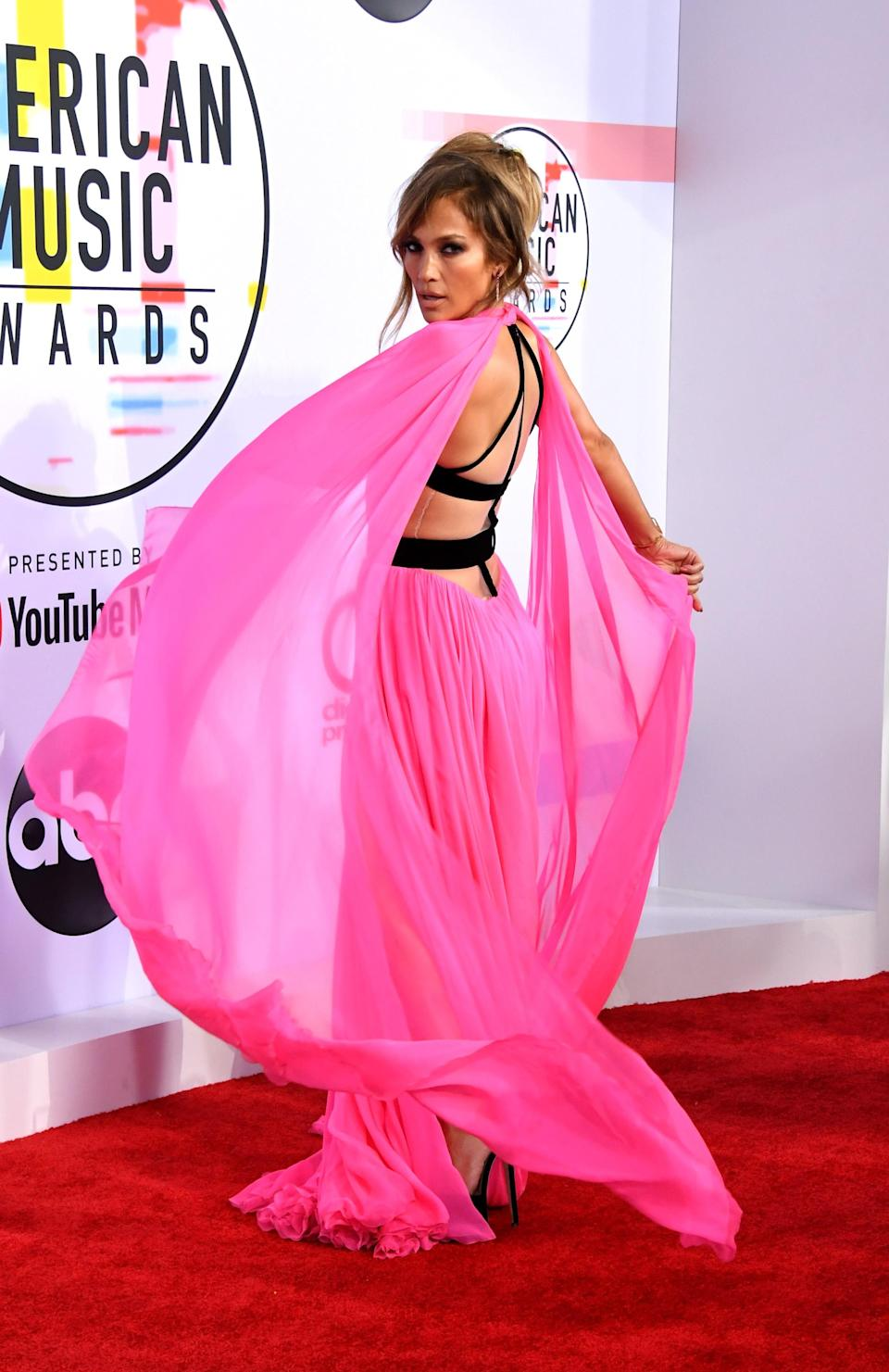 <p>Jennifer Lopez made sure to steal the limelight in a neon pink Georges Chakra dress at the music awards. Not only did the gown feature a plunging v-neck and thigh-high split skirt but an unusual criss-cross back (and cape for good measure). <em>[Photo: Getty]</em> </p>
